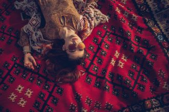 One woman, hippie lying on a blanket, enjoying alone.