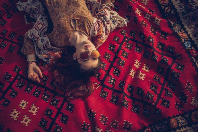 One woman, hippie lying on a blanket, enjoying alone.