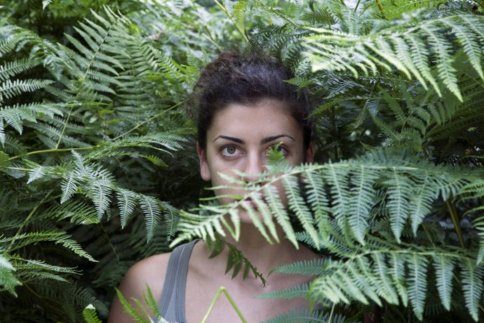 Young woman among ferns