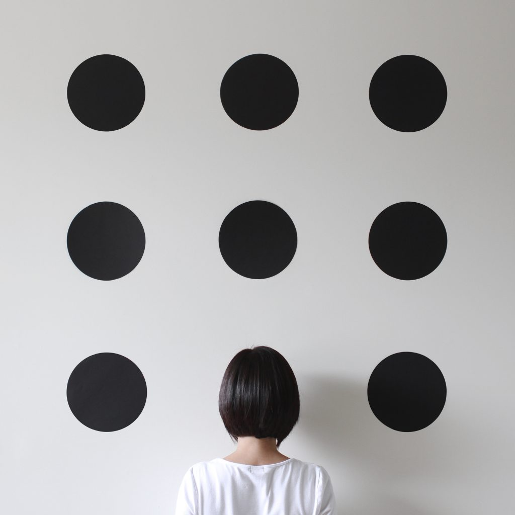 Woman facing a wall with dots
