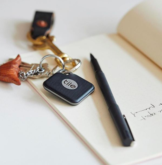 Tile bluetooth tracker on keys sitting on a notebook