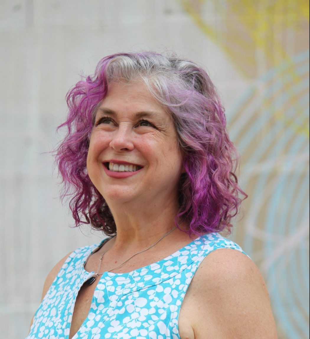Debra looking up and smiling with a blue shirt and hair dyed purple