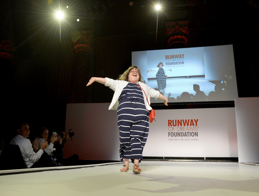 Sara walking down the fashion runway, arms in the air, wearing a navy blue striped jumpsuit and white sweater