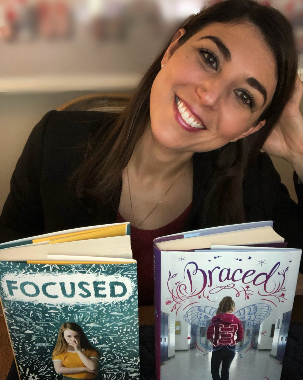 "Alyson smiles with her two books, ""Focused"" and ""Braced"""