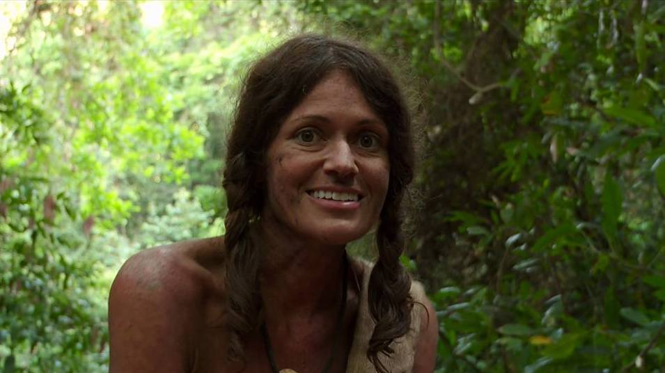 Tara smiles in the jungle, hair unbrushed and dirt on her face