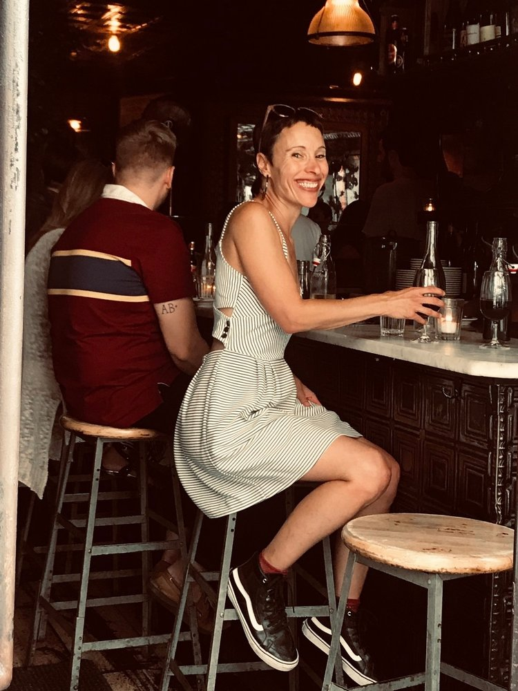 Emily smiles, sitting on a bar stool wearing a sun dress and sneakers