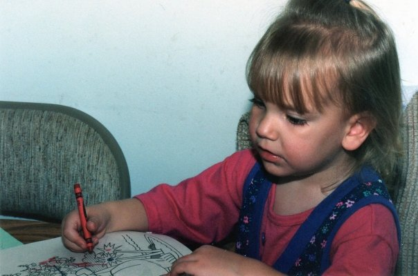 Dani as a young girl drawing with a red crayon