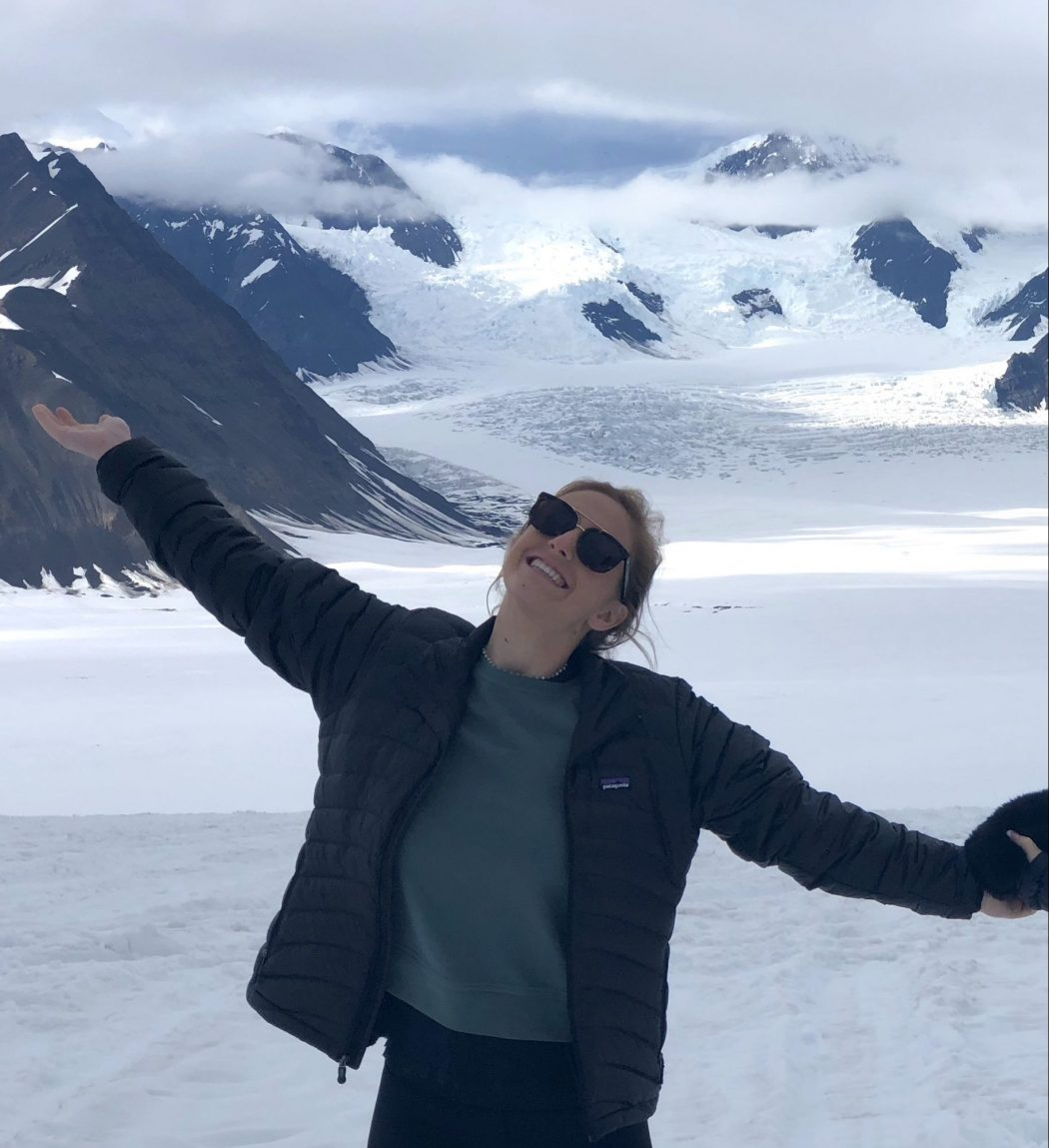 Mackenzie smiling with arms outstretched, snowy mountains in the background