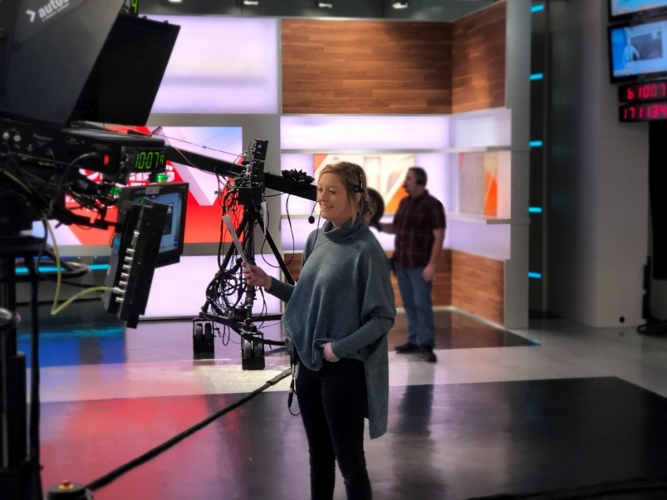 Mackenzie on the floor of a newsroom behind camera equipment looking at playback on a monitor. She is wearing a headset and smiling.