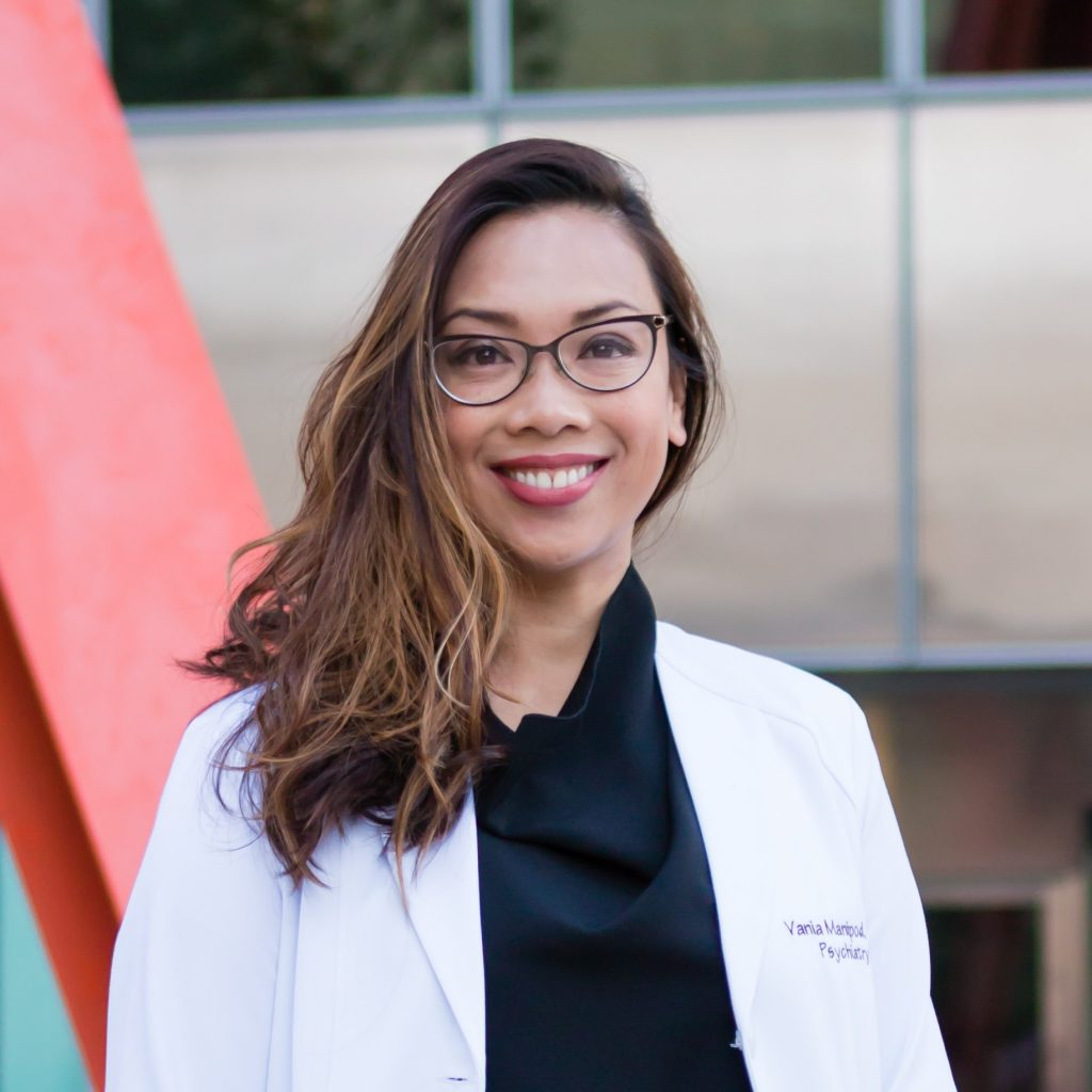 Dr Vania smiles wearing a white medical coat and glasses