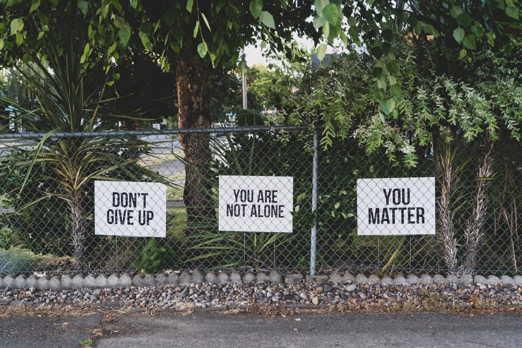 Signs on a chain link fence. Don't give up. You are not alone. You matter.